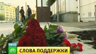 Москвичи несут цветы и свечи к посольству Франции