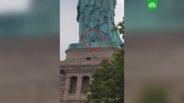 Полиция Нью-Йорка пытается снять со статуи Свободы участницу акции протеста.США, митинги и протесты, памятники.НТВ.Ru: новости, видео, программы телеканала НТВ